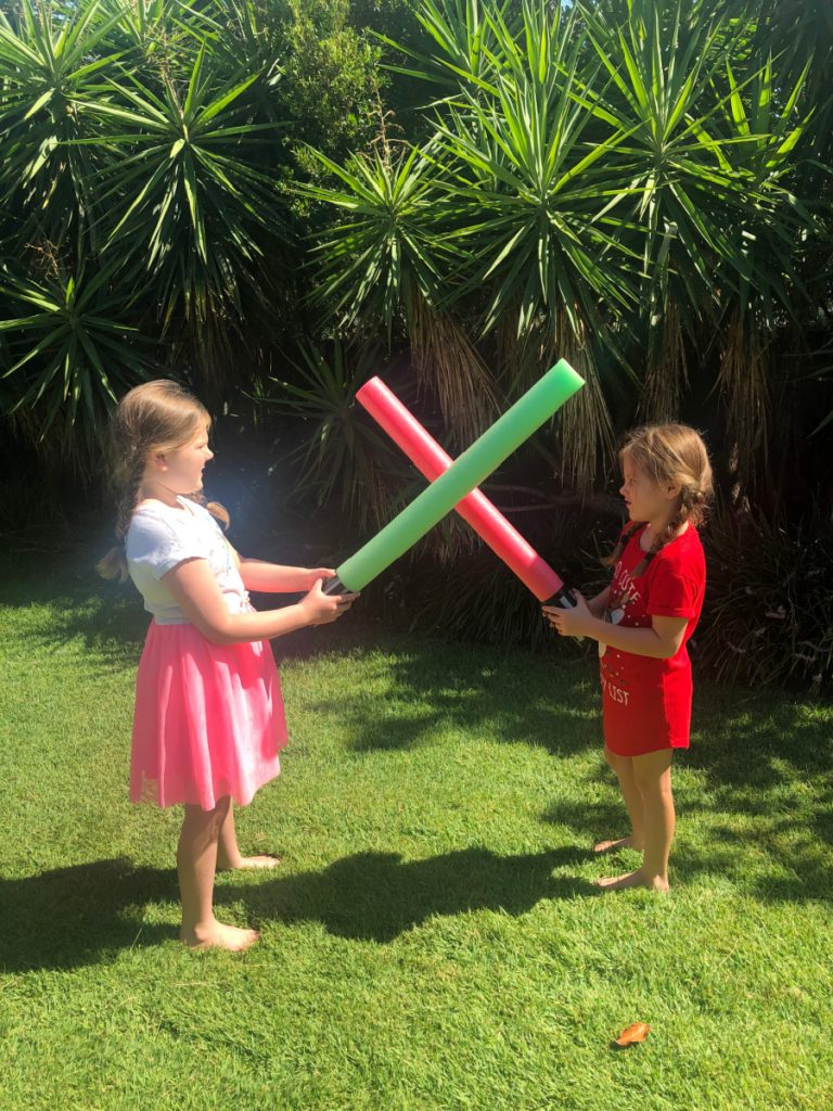 playing with lightsabers in backyard