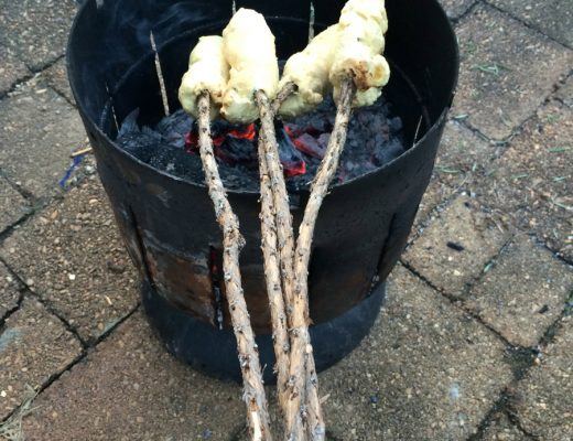 Damper on a stick green tree twists on rosemary stick cooking one hand